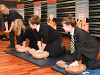 Schoolchildren learning CPR