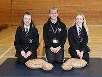 Teacher and pupils posing with resus manikins